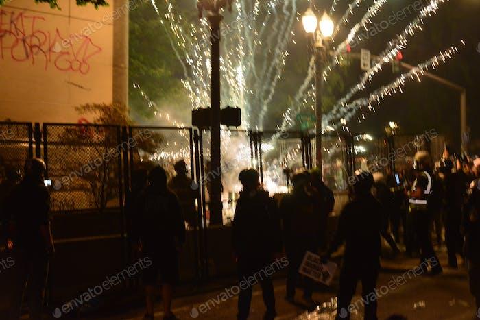 Un fuegos artificiales explota cerca de los manifestantes y la policía durante la protesta de Portland.