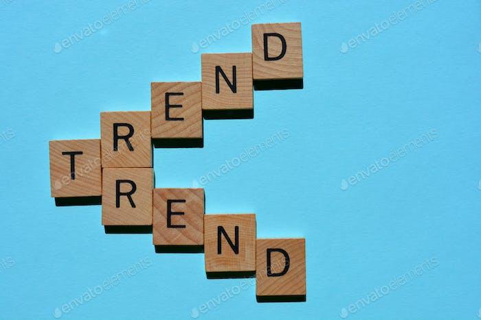 Tendencia, palabras en letras del alfabeto de madera 3D aisladas sobre fondo azul