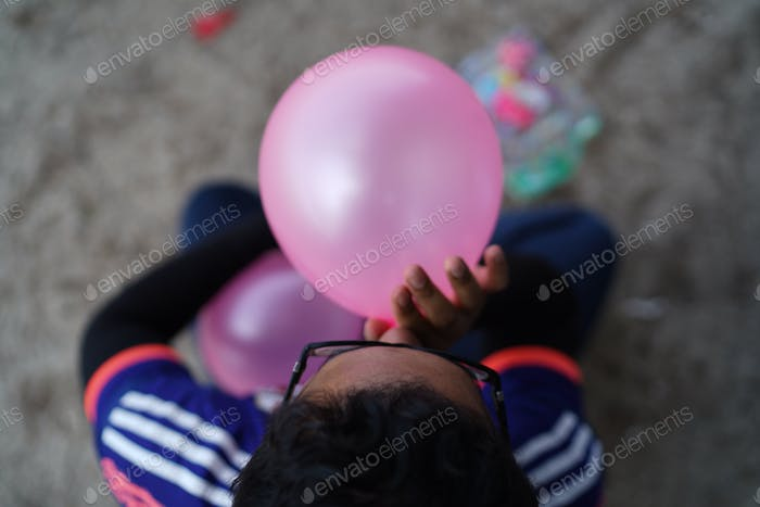 Top shot of a guy blowing a pink colour balloon