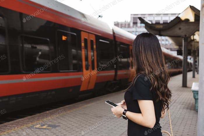 Woman using mobile at train station