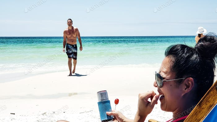 Generation X woman laughing at the beach while her husband leaving the sea wonders if its him....