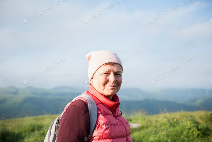 Happy senior woman hiking with backpacks in mountainous area. healthy lifestyle, leisure activity