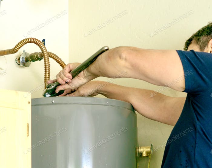 Adult male using a wrench to make adjustments on top of a hot water heater