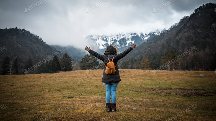 Rear view of woman with outstretched arms standing on field under mountain.