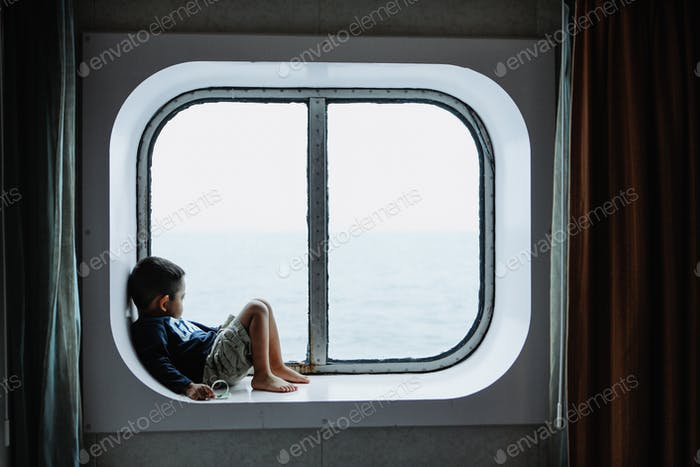 A young boy looking out a window deep in thought.