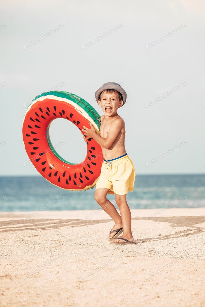 A little boy with watermelon swimming circle at the beach