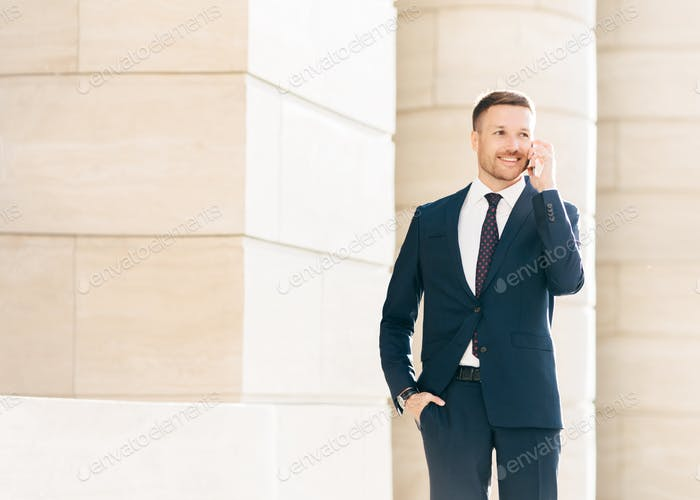 Attractive male CEO solves working issues with business partner during phone conversation
