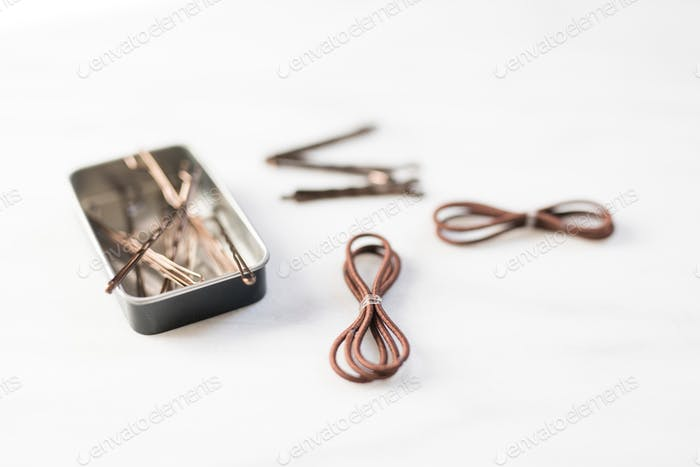 View of brown bobby pins in a tin and brow hair bands on a white blank background