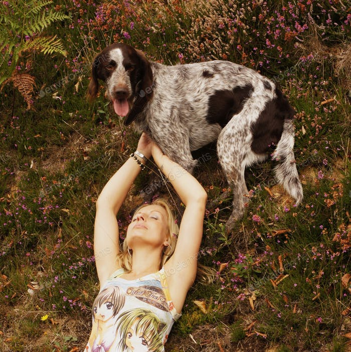Blonde girl with her arms raised lying on her back on the grass with her dog standing at the top