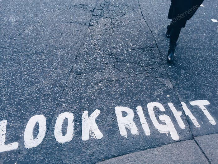 Pedestrian crossing: look right, walking person, gray floor, white letters, urban life, outdoors