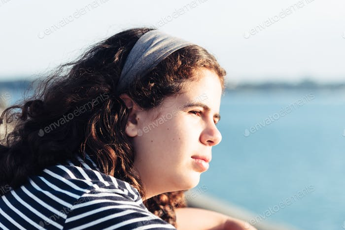 Headshot portrait of beautiful girl looking at the sea against sun with space for copy
