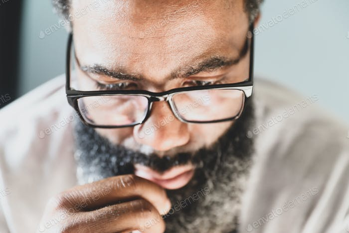 A bearded man deep in his thoughts