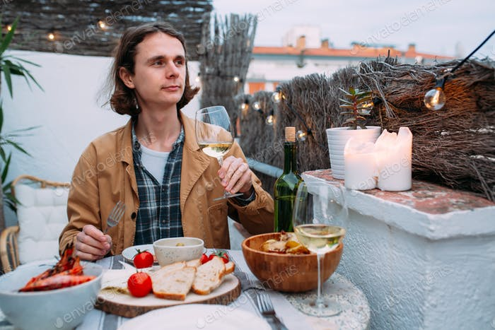 hadsome hipster millenial man sit on the nice terrace having dinner barbeque and drinking wine
