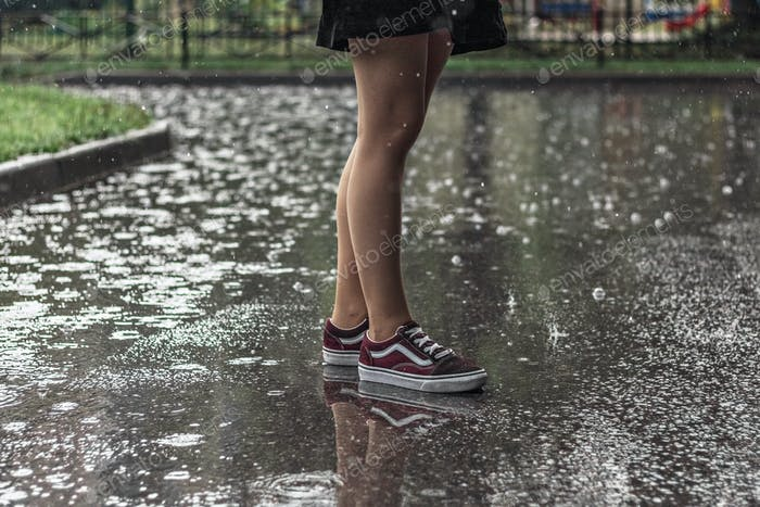 Feet of a young girl in sneakers in the summer rain.