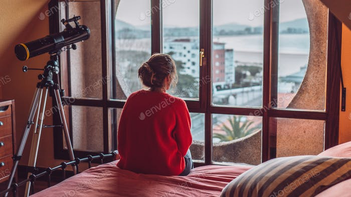 Girl looking through the window of her room sitting on the bed. In the background is the beach