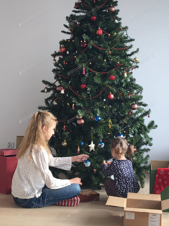 Little girl and her elder sister decorating a christmas tree