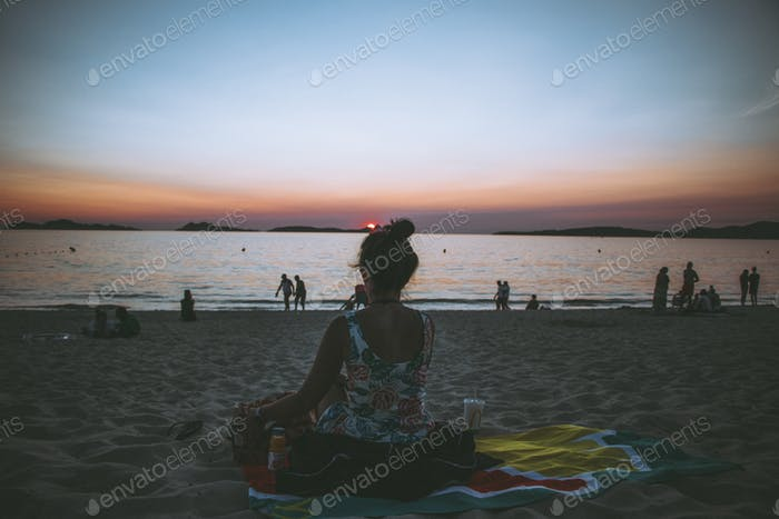 Millenial woman sitting in a towel. Sunset. Earth tones. Summer vibes. Lifestyle.