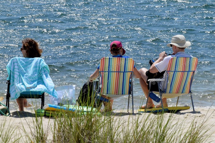 People enjoying a sunny afternoon at the beach on Cape Cod while sitting in beach chairs