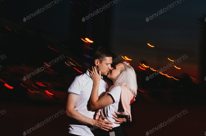 Young happy couple in love kissing in the night cuty street. Photo with flash effects