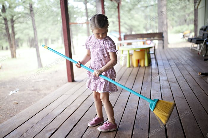 girl sweeping the porch at the cabin