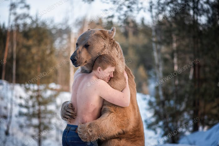 Half-naked man hugs a brown bear in a winter forest
