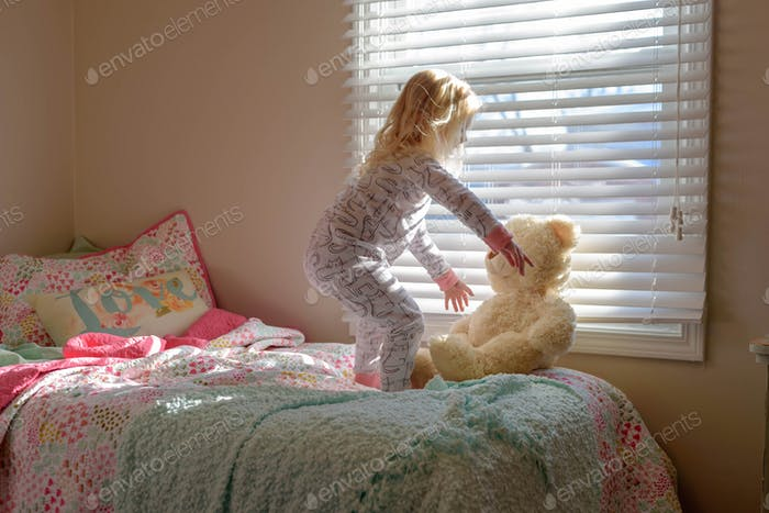 Rise and shine! Little girl reaches for her teddy bear in the morning sunlight -  home, family life,