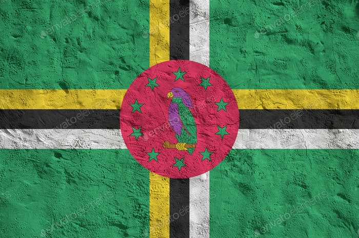 Dominica flag depicted in bright paint colors on old relief plastering wall close up