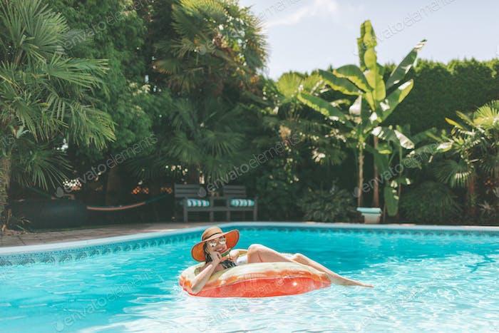 Eine Frau isst Wassermelone, während sie in einem Innenrohr in einem Schwimmbad schwimmt.