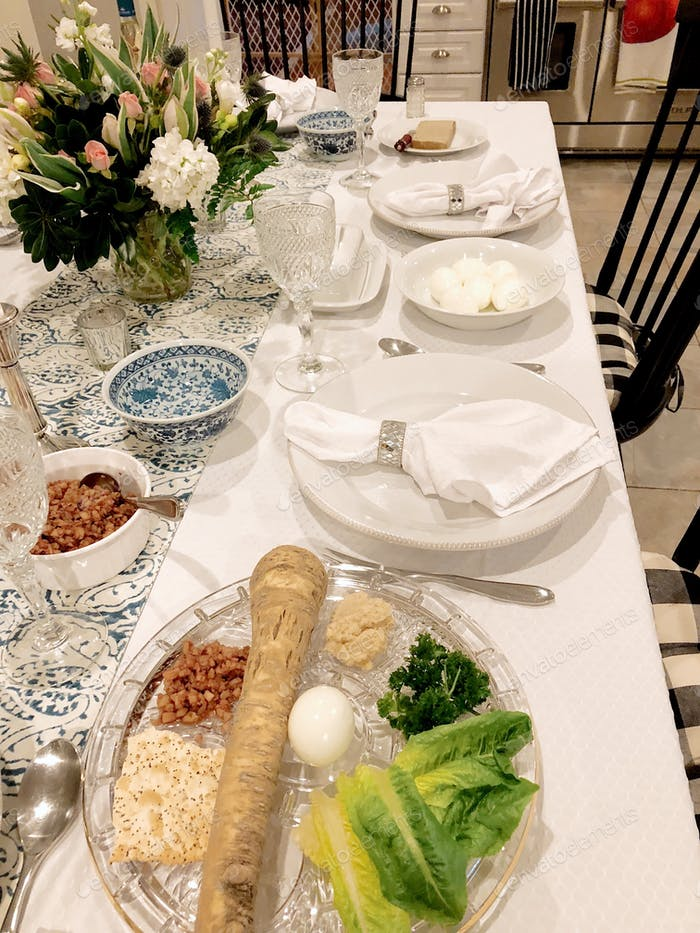 Table set for Passover Seder with a Seder plate prominent in the foreground.