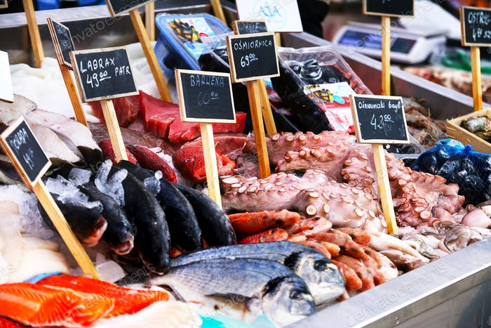 Seafood market with price labels written in Polish language.