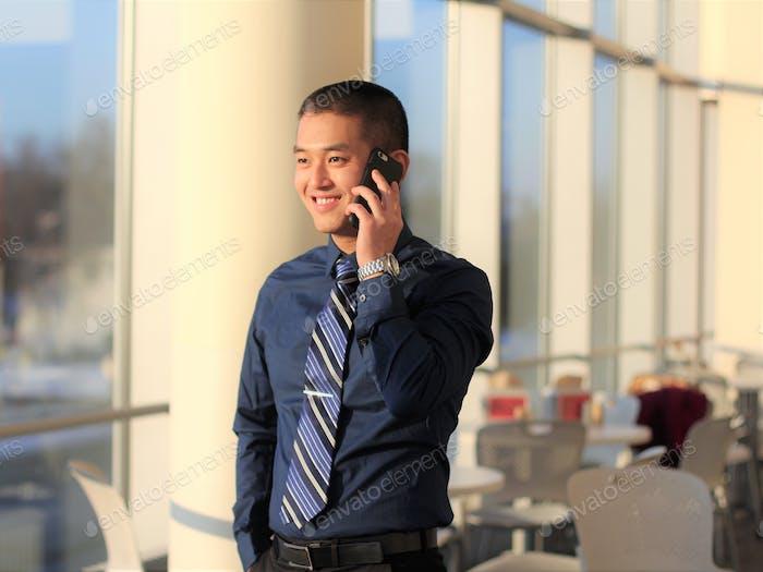 Professionell gekleidet asiatischen Millennial Mann sprechen am Telefon