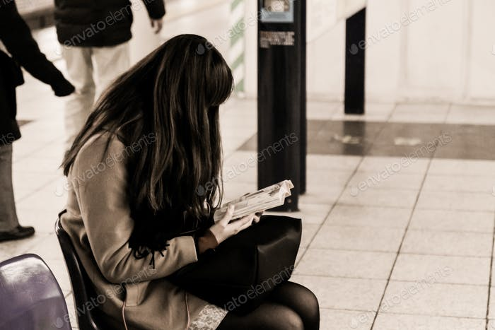 Girl reading a book in a public place