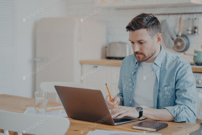 Handsome young man using laptop computer at home
