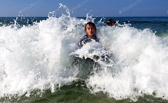 Little boy riding a monster wave at least 2 feet tall....