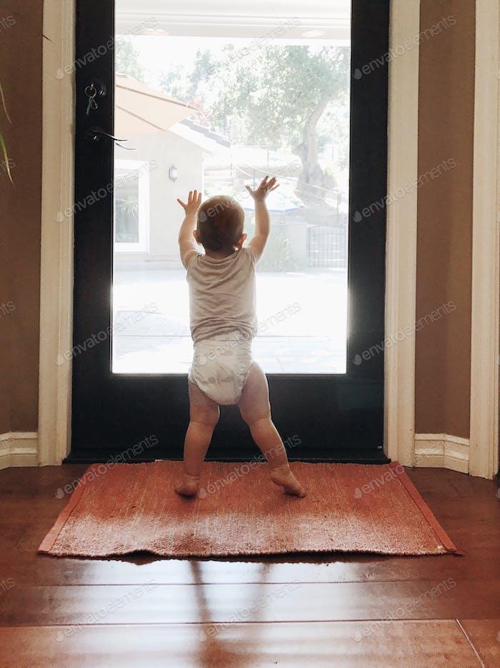 Baby standing against glass door