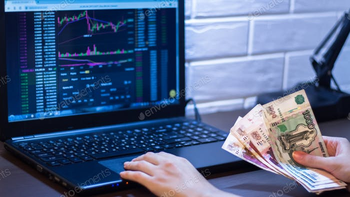 Hands holding Russian rubles in front of a computer monitor with the currency market and Forex