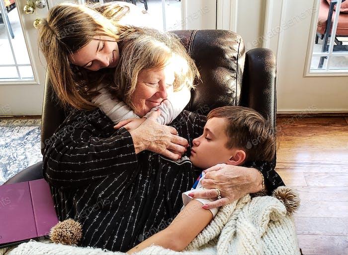 Liebevolles Foto von Oma hält einen schlafenden Enkel, während Enkelin umarmt die Großmutter w