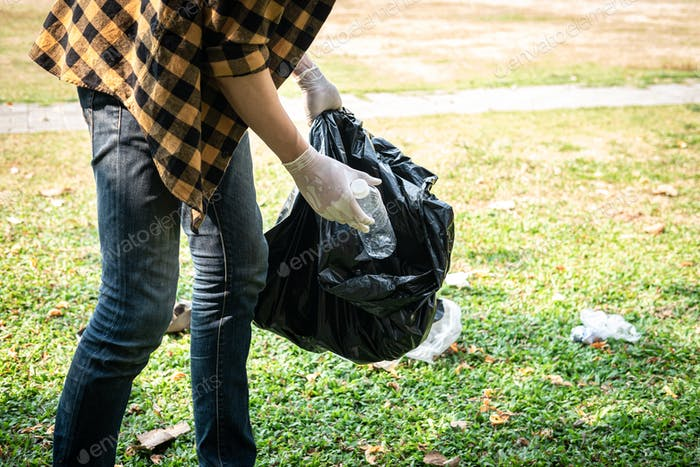 Volunteer man in gloves to collect plastic bottles into plastic black bag for cleaning the park