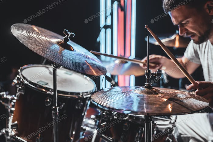 A male drummer plays drums with drum sticks.