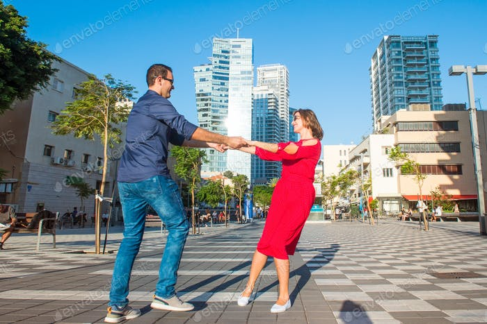 Emotional young happy couple in bright clothes and sunglasses having fun on the city square