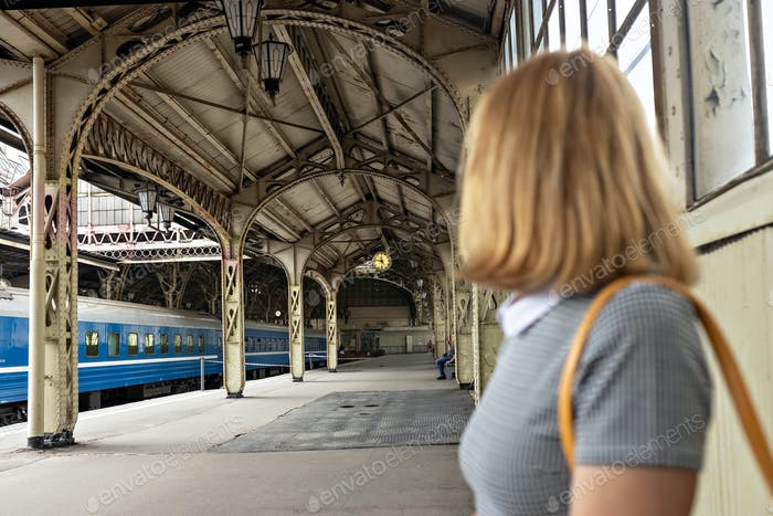 A platform at a railway station with a young female passenger and a train. The old railway station.