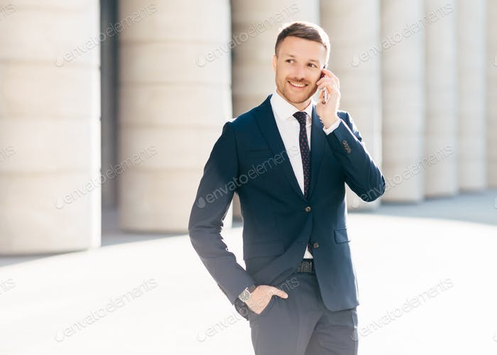 Successful male manager satisfied with mobile tariffs, makes phone call,  wears formal suit