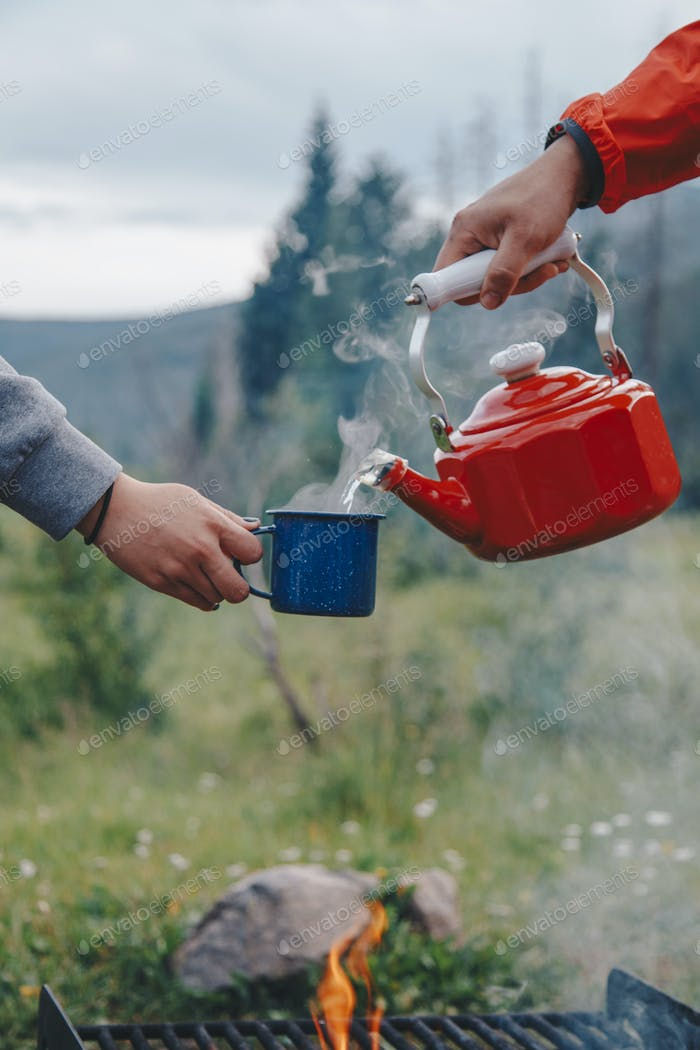 Pouring hot water in a coffee cup at a campsite