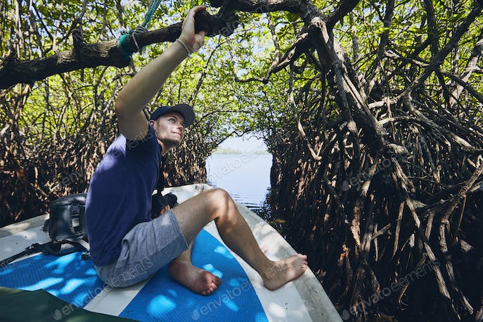 Young man during boat trip through mangrove forest in Sri Lanka.
