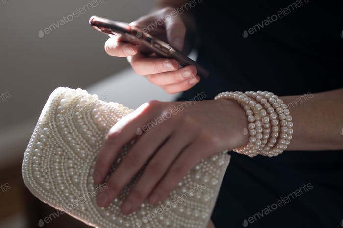 View of a woman seated wearing a black dress holding her mobile phone cell using it to keep up to