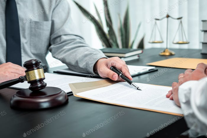 Male lawyer discussing negotiation legal case with client meeting with document contact in courtroom