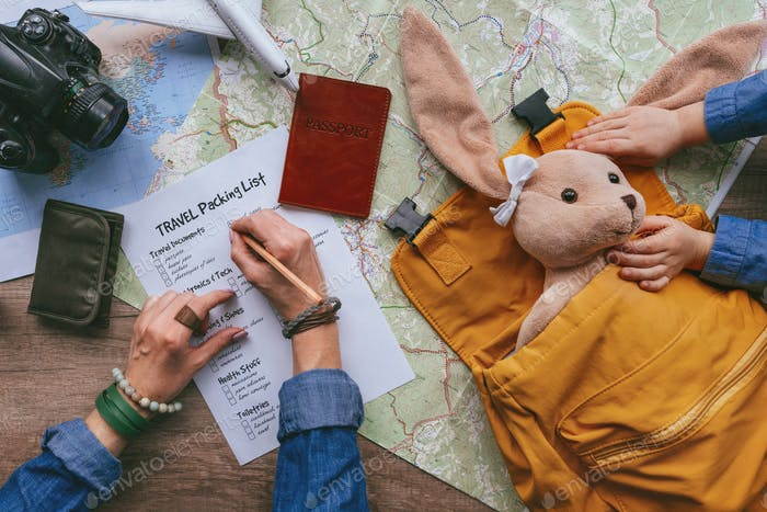 Family preparing for travel. Travel essentials on the wooden background. Top view, flat lay.