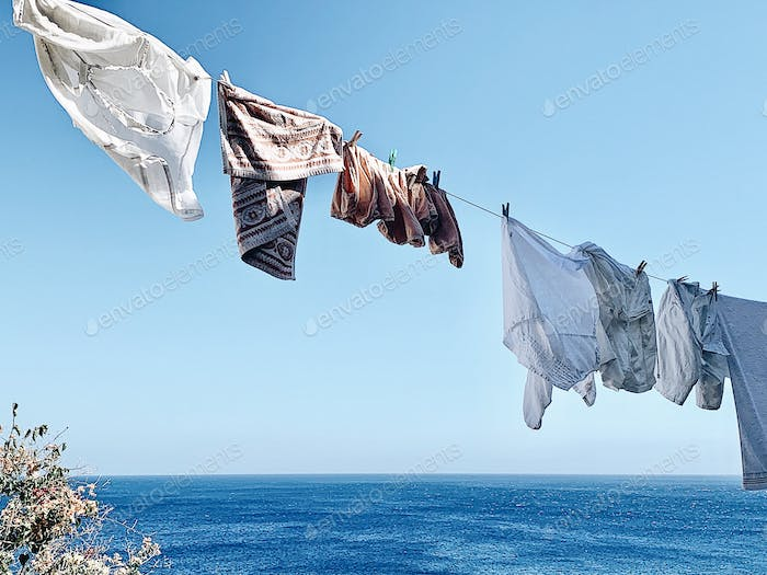 Clothes hanging on a clothesline drying in the wind with the blue sky and sea behind