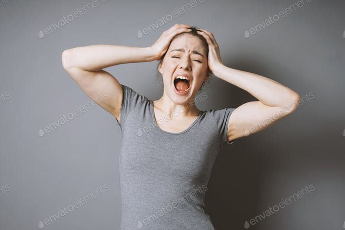 Una joven estresada lanzando una rabieta. Está sosteniendo su cabeza y gritando.
