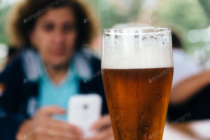 Nahaufnahme eines erfrischenden Pint Lagerbier gegen eine Frau, die auf dem Smartphone schreibt. Selektiver Fokus
